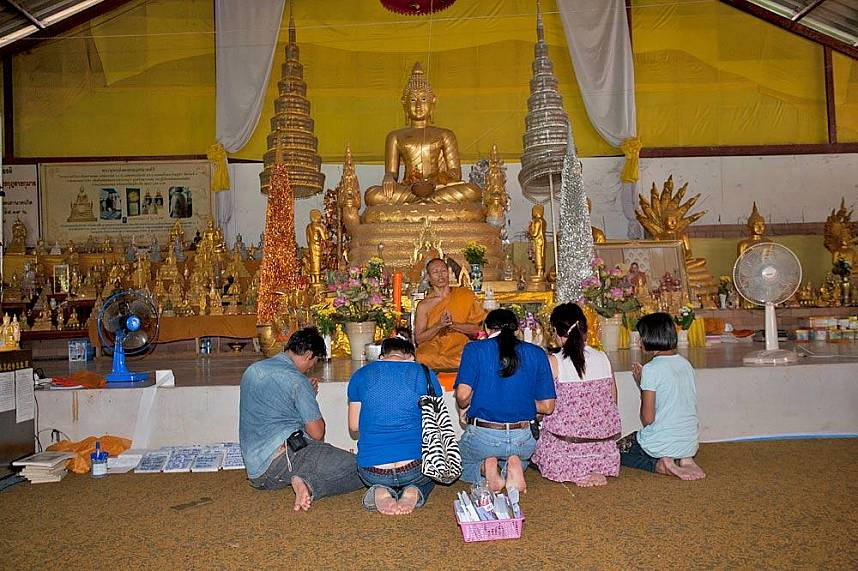Worshipers offer alms to a monk at Phuket Big Buddha Mountain