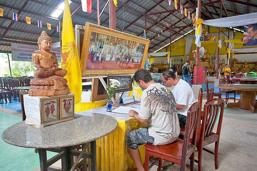 Western tourists sign the visitor book at Big Buddha Mountain Phuket