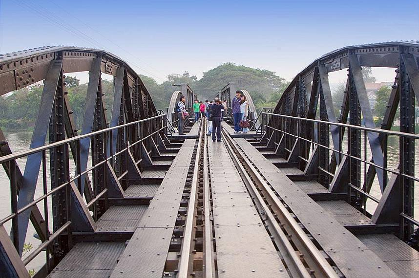 Tourists cross the Bridge Over the River Kwai in Kanchanaburi by foot