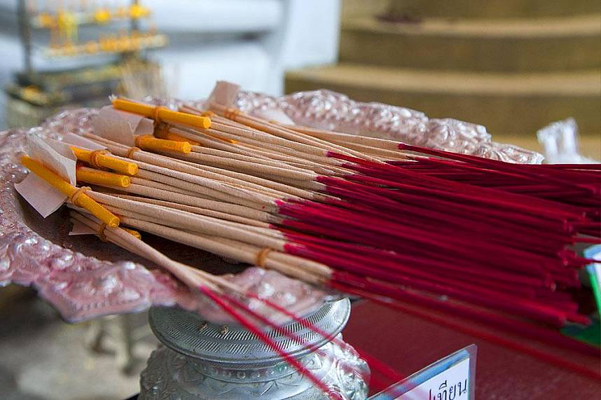 Incense sticks with a candle and golden leaves at the shrine of the Mummiefied Monk in Koh Samui