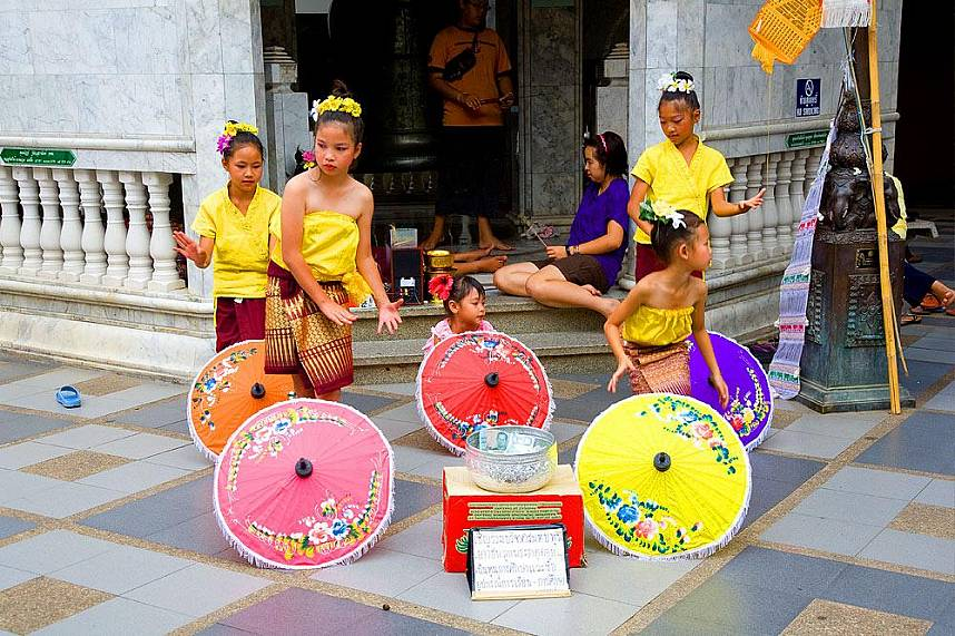 Some young girls show a cultural dance performance in front of a shrine at Doi Suthep Temple in Chiang Mai