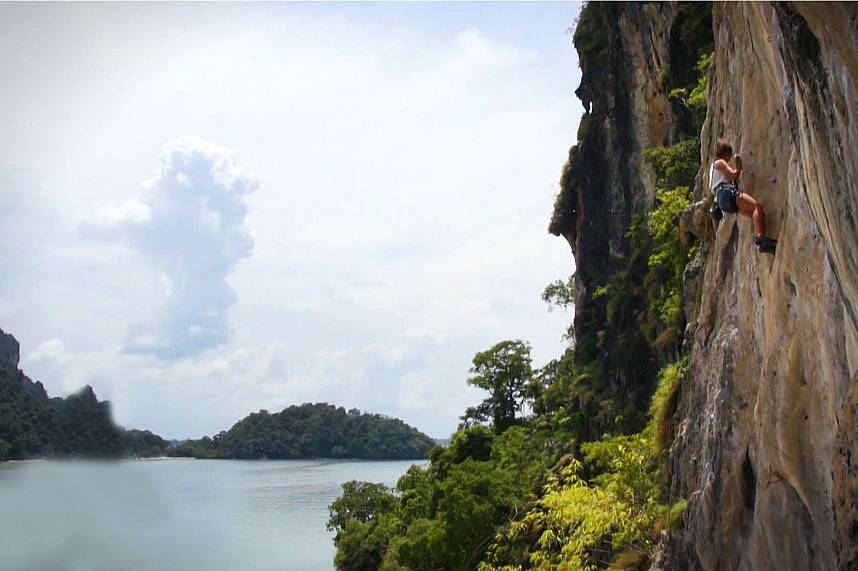 a rock climber conquer a vertical cliff at Railay Beach Krabi