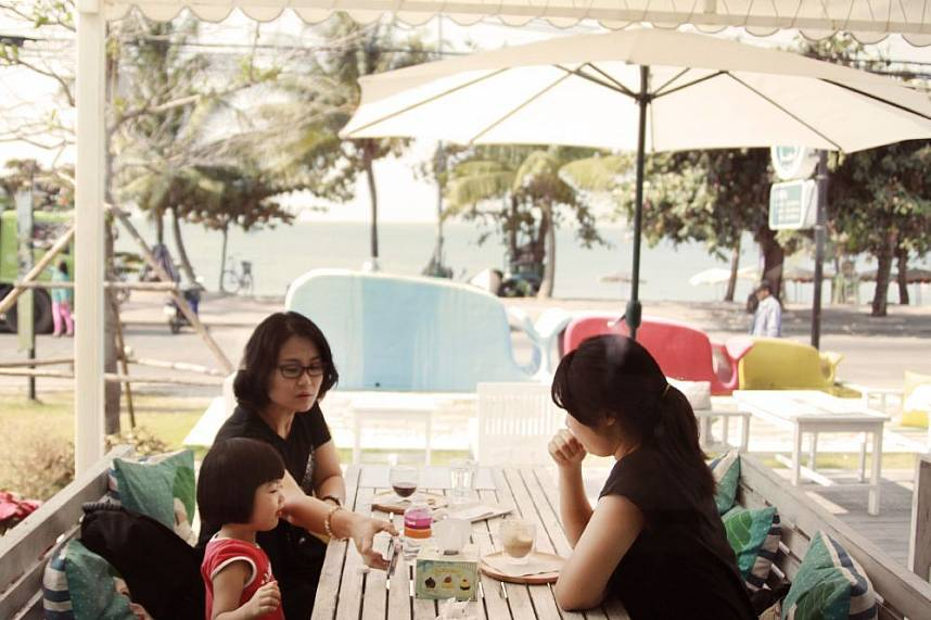 A family has a break under an umbrella at Jomtien Coffee and Sweets