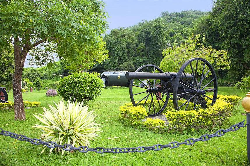 Old army objects are displayed in a garden at Sattahip Toei Ngam Beach