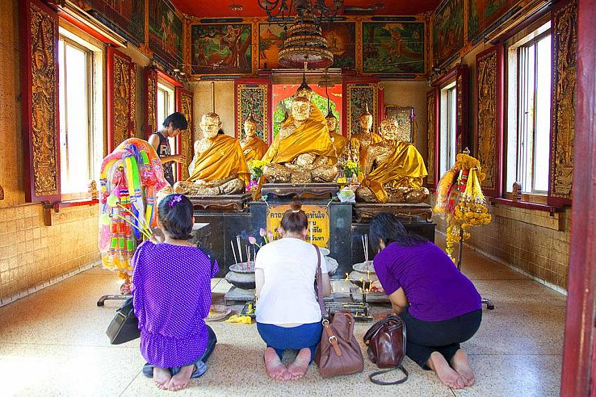 Thai visitors pray at a temple on Koh Loy Tropical Island near Pattaya