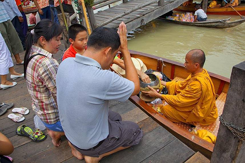 A monk receive alms from Buddhists at Floating Market Pattaya