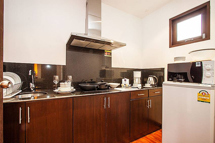 A refrigerator and microwave in the kitchen and facilities of Niranon villa 12