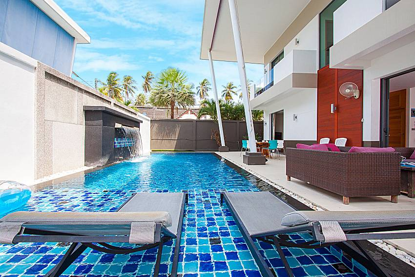 Sun bed near swimming pool and property Villa Elina in Phuket