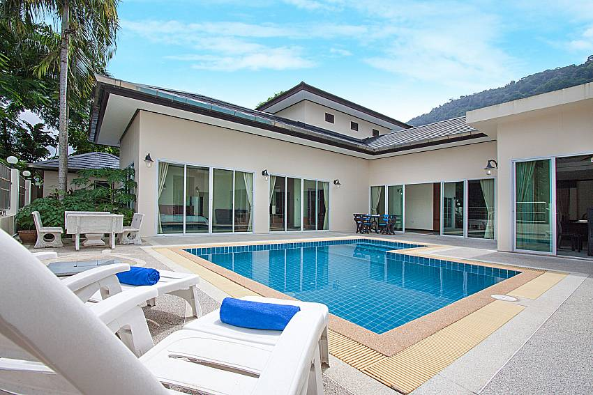 Sun bed near swimming pool and property Villa Aruma in Phuket