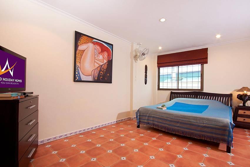 King-size bed with TV at Nai Mueang Klang Villa in Pattaya
