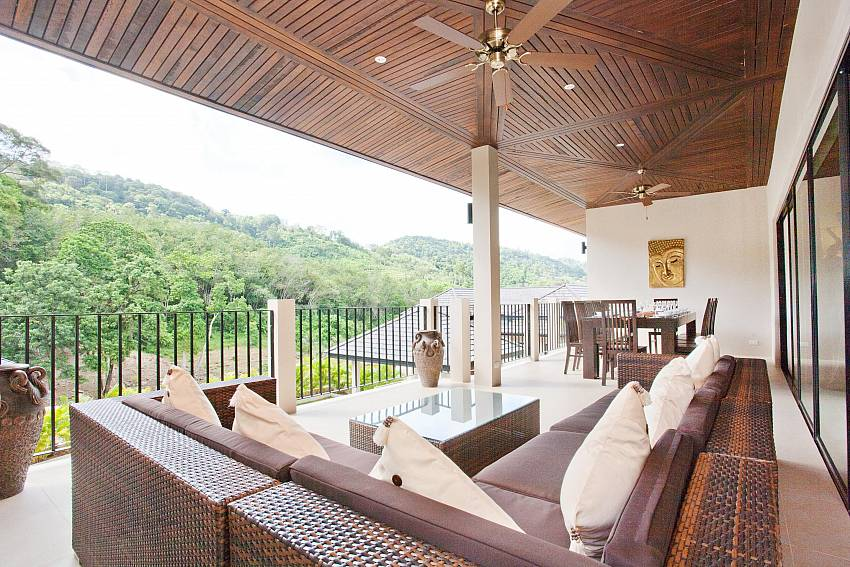 Outdoor lounge with dining table at Waew Opal Phuket