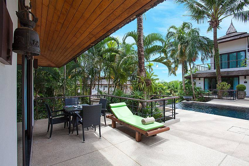 Dining area with sunchair and communal pool at Nirano Villa 25 Phuket