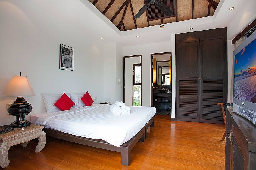 Guest bedroom with TV and en-suite bathroom in Nirano Villa 25 Phuket