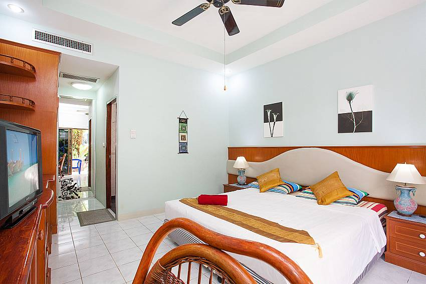 King size bed with TV, aircon and ceiling fan at Apartment Khuno 103 Phuket
