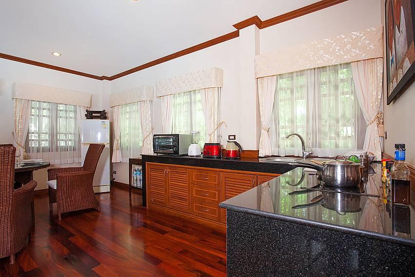 Modern kitchen with dining table at Villa Armorela 201 Phuket