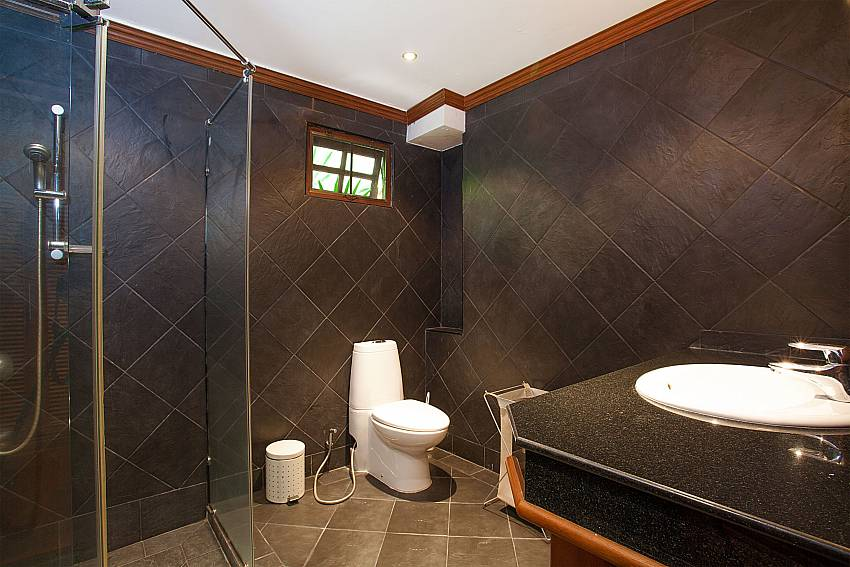 Master bathroom with shower, wash basin and toilet at Villa Armorela 201 Phuket