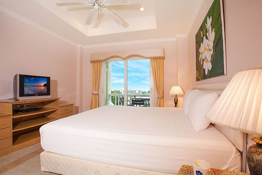 Kingsize bed with TV and balcony at Manuae Condo 202 Phuket