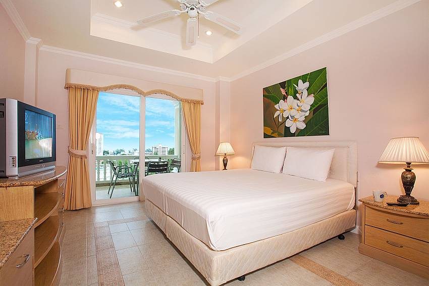 Master bedroom with balcony access at Manuae Condo 202 Phuket