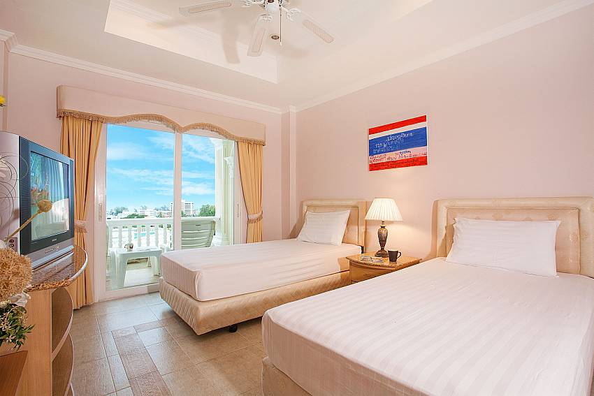 Guest bedroom with balcony access and TV at Manuae Condo 202 Phuket