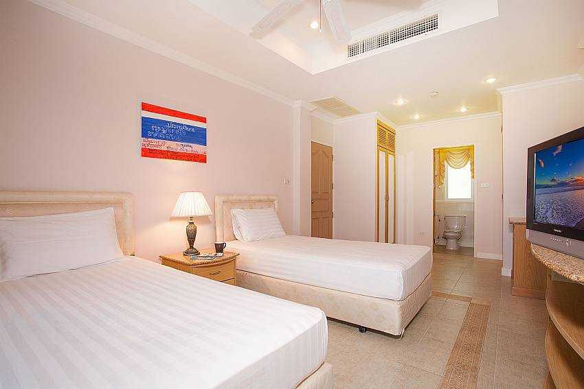 Guest bedroom with 2 single beds and TV in Manuae Condo 202 Phuket