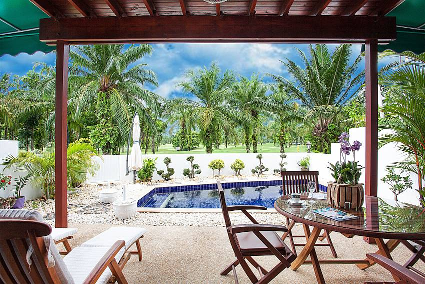 Sun loungers and dining table by the pool of Villa Dooriya Phuket