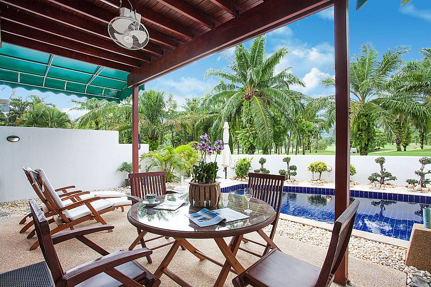 Outdoor dining and sun chairs by the private pool of Villa Dooriya Phuket