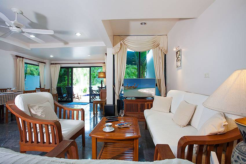 Sitting area with pool view and TV at Villa Dooriya in Central Phuket