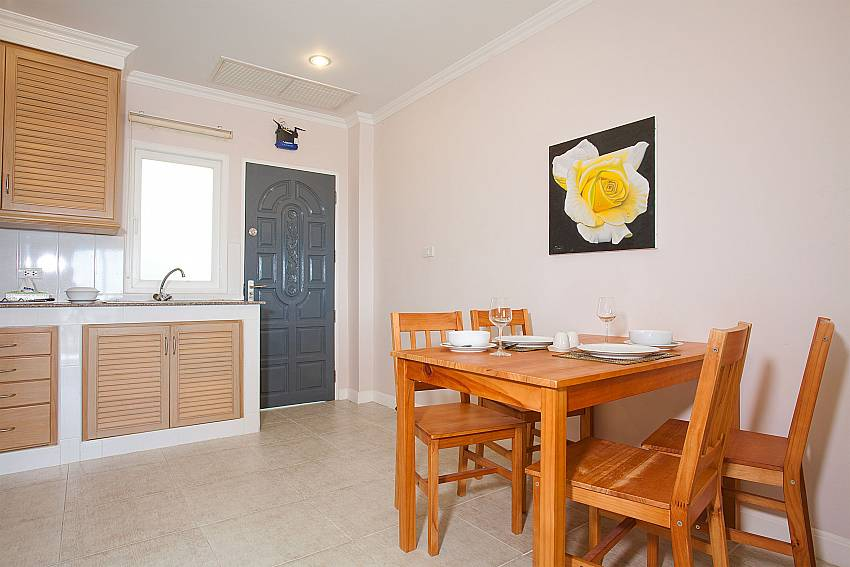 Dining area with kitchen at Manuae Condo 102 in Karon Phuket