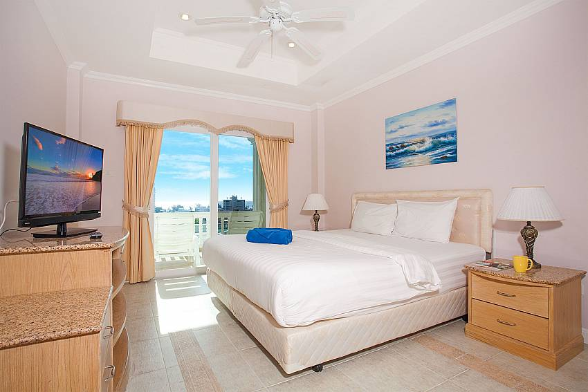 Bedroom with TV and balcony access at Manuae Condo 102 Phuket