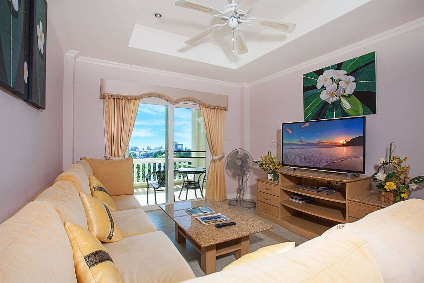 Living room with TV and private balcony at Manuae Condo 201 Phuket