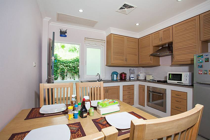 4 seat dining table and kitchen at Manuae Condo 201 in Westphuket