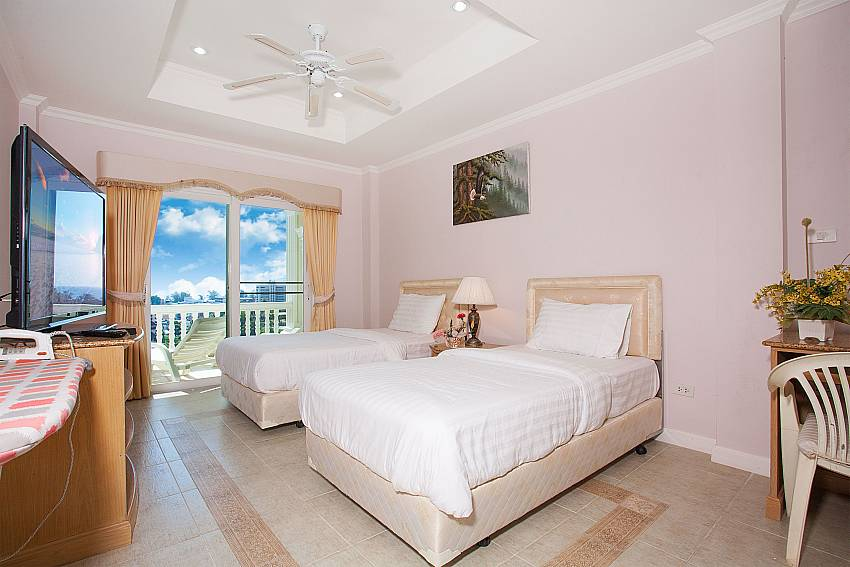 Guest bedroom with private balcony access in Manuae Condo 201 Phuket