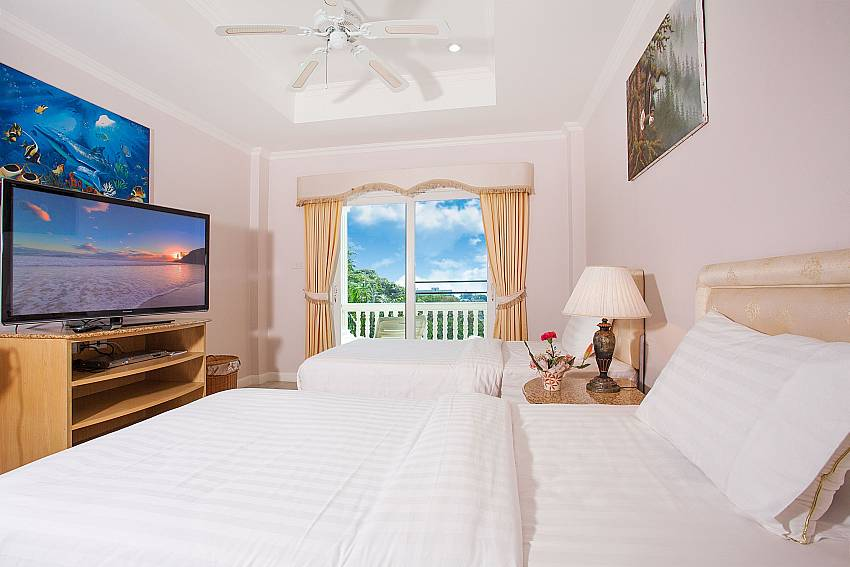 Twin beds in guest bedroom with TV and view at Manuae Condo 201 Phuket