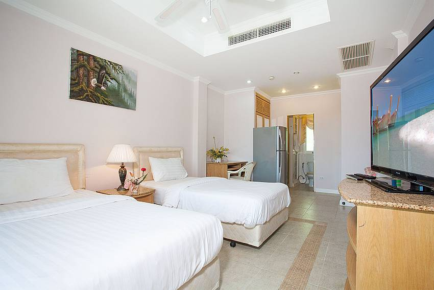 2. bedroom with two single beds and TV in Manuae Condo 201 Westphuket