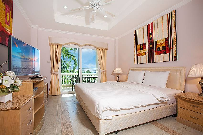 Master bedroon with TV and private balcony access at Manuae Condo 201 Phuket