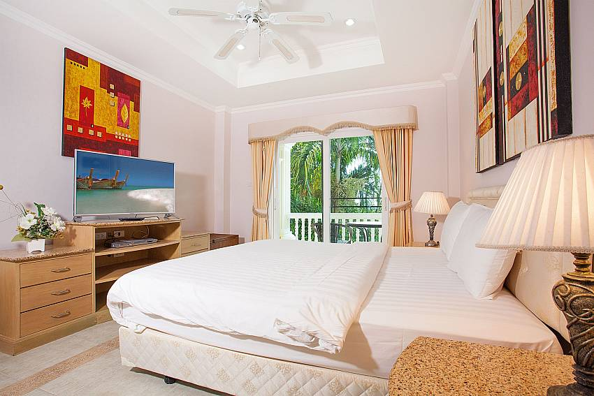King size bed and TV in master bedroom at Manuae Condo 201 Phuket