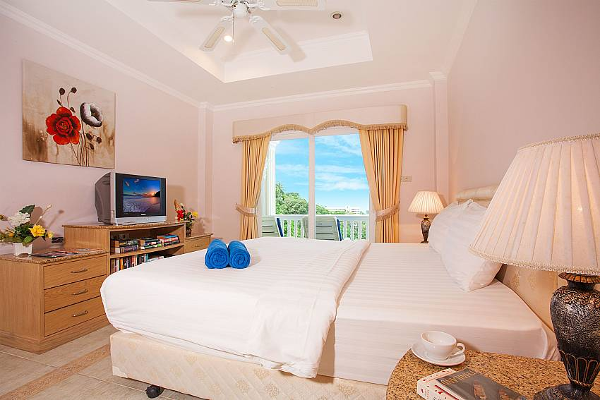 King size bedroom with TV and balcony access at Manuae Condo 101 Phuket