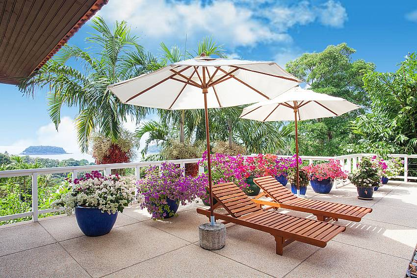 Pool deck with sun beds and umbrellas at Ruedi Villa Phuket