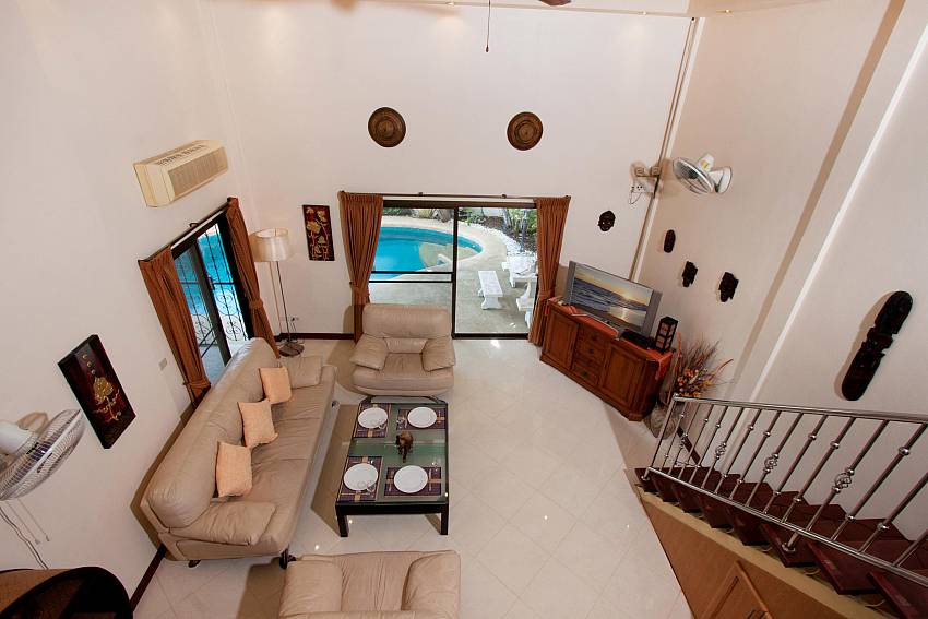 Living area with TV and pool view at Nai Mueang Noi villa Pattaya