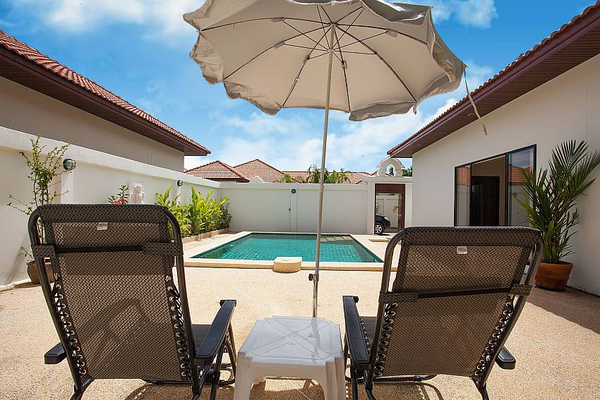 Sun beds with umbrella by the private pool of Insignia Villa Pattaya
