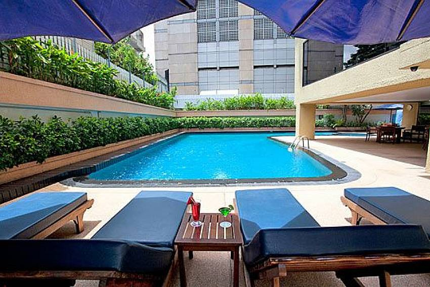 Sun bed by the pool Of Sala Daeng Deluxe Suite Room 605