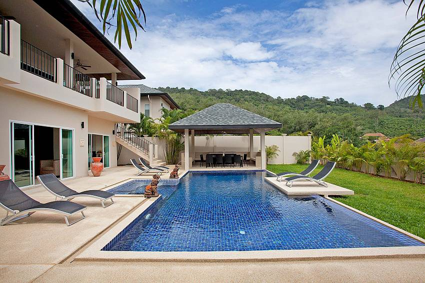 Private pool with sun chairs and dining pavilion at Villa Ampai Phuket