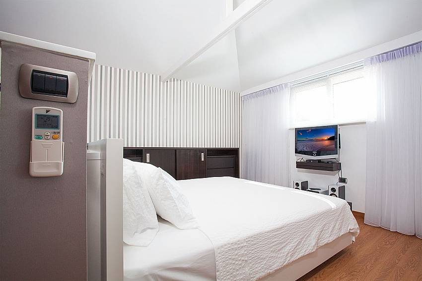Modern bedroom with king-size bed and TV at Pratumnak Regal Villa