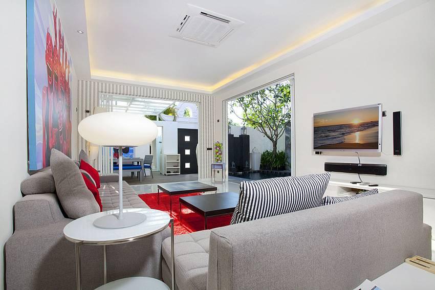 Living room with sofa and TV at Pratumnak Regal Villa in Pattaya