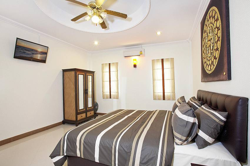 3. Bedroom with wardrobe and TV at Villa Patiharn in Pattaya