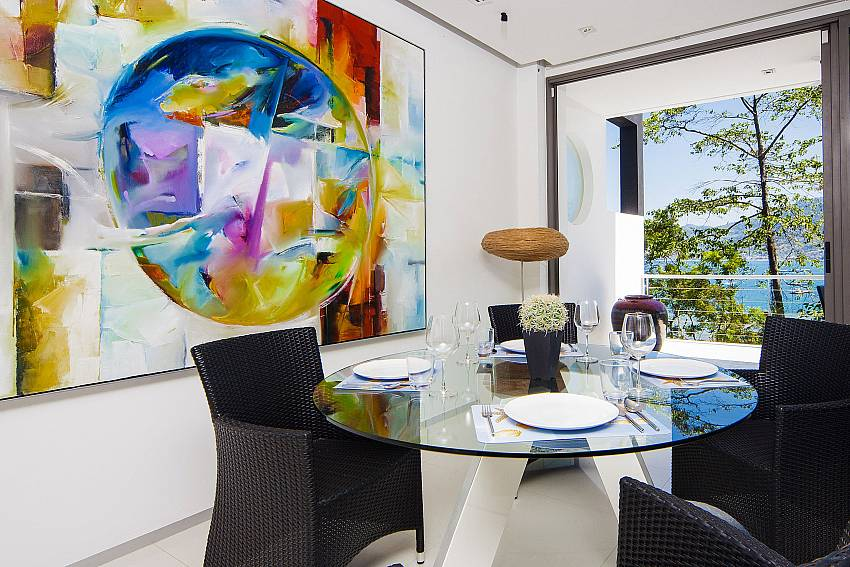 Dinning table with the walls are decorated with artistic drawings Of Seductive Sunset Villa Patong A5