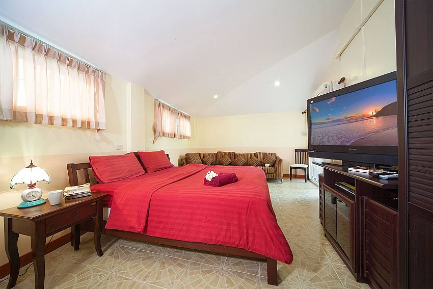 Bedroom with kingsize bed, TV and sofa at Baan Chokdee Pattaya