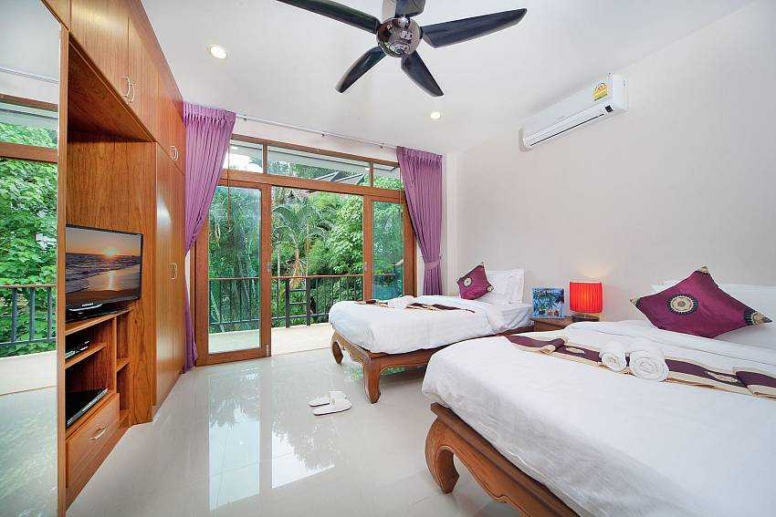 Double bedroom with TV and shelves overlooking outdoor Of Patong Hill Estate Seven (Five)