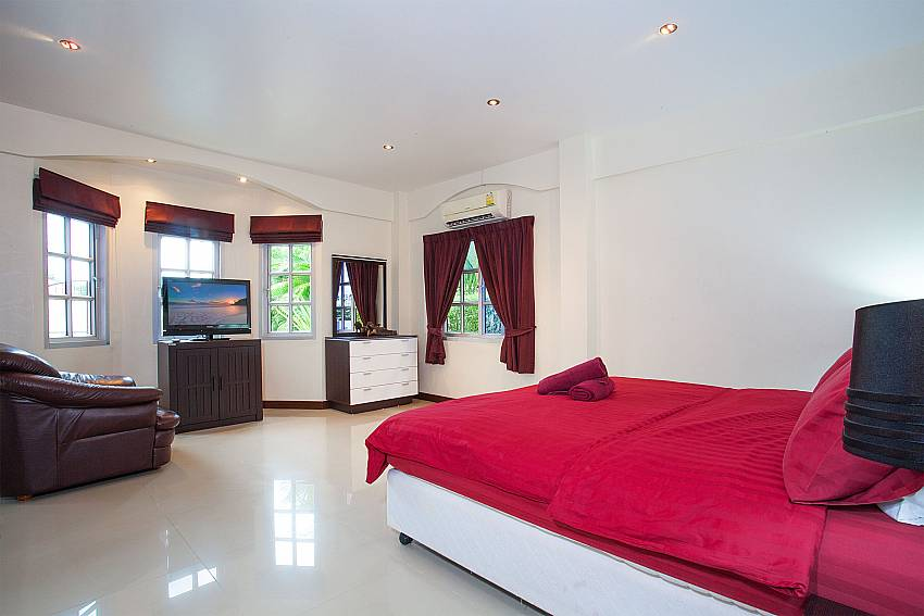 King size bed with TV and sofa in Baan Duan Pattaya