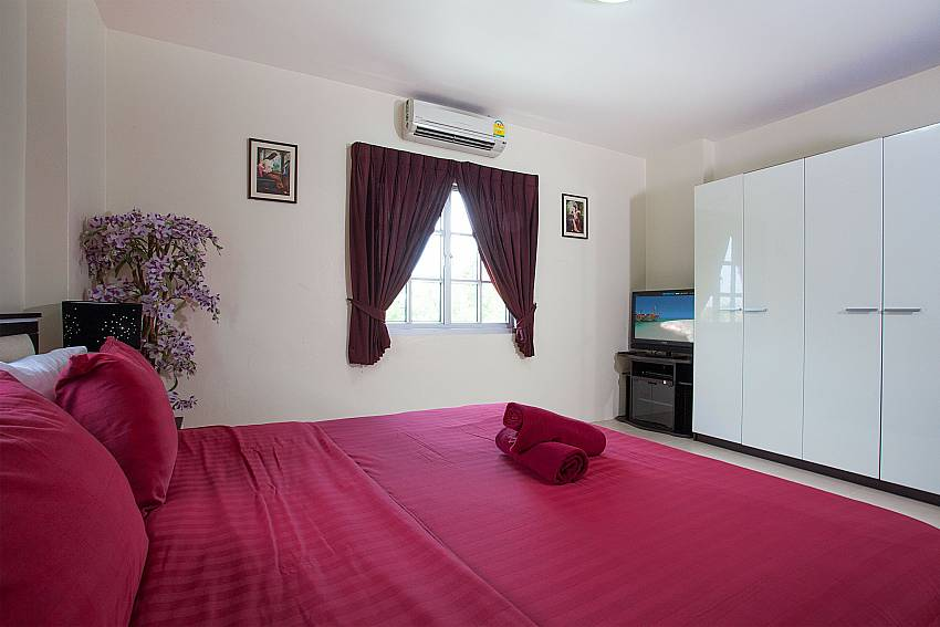 Master bedroom with king-size bed and TV at Baan Duan Pattaya